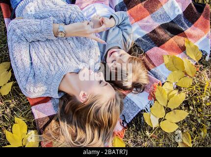 Vista superior joven madre acostada con su hija pequeña en la manta y sonriendo mientras se divierten en el parque de otoño. Niña pequeña jugando con su mamá mientras layi