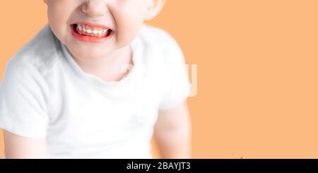 Un niño pequeño y hermoso se ríe mientras muestra sus dientes blancos