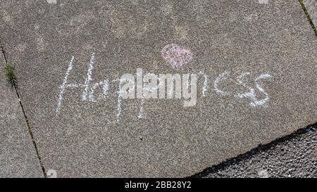 Palabra felicidad escrito en el pavimento con tiza blanca. Con corazón rosa como punto para el i. Concepto para el pensamiento positivo, sentirse feliz, buenas vibraciones.