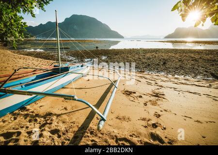 Bangka barco en la playa de arena con luz dorada puesta de sol sobre las islas tropicales en el fondo. Bahía el Nido. Filipinas