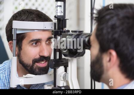 Macho médico oftalmólogo es controlar la visión del ojo del apuesto joven en la moderna Clínica. El médico y el paciente en oftalmología clínica.