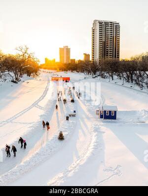 Patinaje sobre hielo en el sendero del río Assiniboine al atardecer, parte del sendero Red River Mutual Trail, The Forks, Winnipeg, Manitoba, Canadá