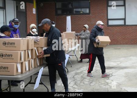 Philadelphia, Estados Unidos. 30 de marzo de 2020. El voluntario ayuda a los miembros de la comunidad a recoger uno de los 200 paquetes disponibles de comida gratis en un lugar de distribución, en la sección noroeste de Filadelfia, PA, el 30 de marzo de 2020. El programa coordinado por la Ciudad distribuye dos veces a la semana cajas de comida gratis en veinte lugares de la ciudad a los residentes impactador por la crisis del COVID-19. Crédito: OOgImages/Alamy Live News