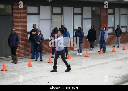 Philadelphia, Estados Unidos. 30 de marzo de 2020. Los miembros de la comunidad esperan en fila para recibir un paquete de alimentos gratis en un programa de distribución, en la sección noroeste de Filadelfia, PA, el 30 de marzo de 2020. El programa coordinado por la Ciudad distribuye dos veces a la semana cajas de comida gratis en veinte lugares de la ciudad a los residentes impactador por la crisis del COVID-19. Crédito: OOgImages/Alamy Live News