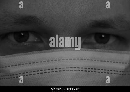 El hombre tiene una máscara médica protectora, anti-infección, protección contra el coronavirus. Gran mirada a la cámara, primer plano. Epidemia pandémica. Enfoque selectivo