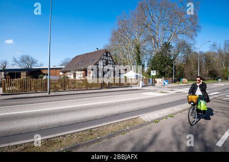 Estrasburgo, Francia - 18 de marzo de 2020: Mujer solitaria en bicicleta vacía habitual calle de intersección ocupada ahora vacía debido al brote de coronavirus