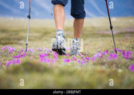 Vista en ángulo bajo de excursionista caminando por el prado alpino en el acrítico.
