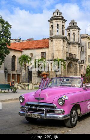Coche clásico en rosa en la Iglesia del Santo Cristo del Buen Viaje, se encuentra en la Habana Vieja, la Habana, Cuba