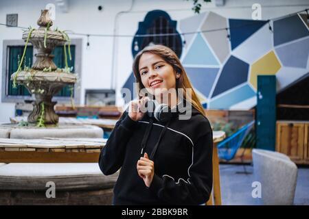 Feliz adolescente latina escuchando música en auriculares en la ciudad de México