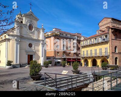 Pequeña plaza de adoquines y la iglesia parroquial blanca de San Giovanni bajo el cielo azul en Alba, Piamonte, norte de Italia.
