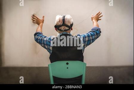 el hombre maduro está mirando a través del espectador de la realidad virtual durante la cuarentena dura en el momento del coronavirus