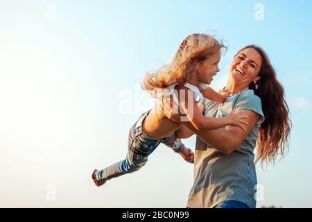Día de la madre. Mujer jugando y divertirse con su hija en el parque de primavera. Feliz madre tirar niño al aire libre.