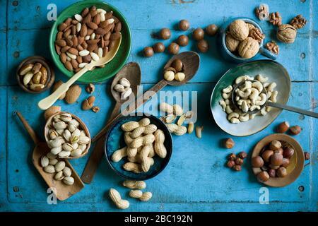 Vista superior de varios frutos secos en cuencos y en cucharas en una mesa rústica azul