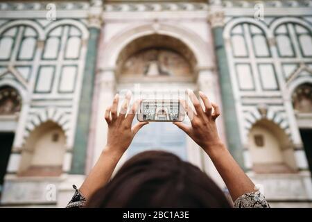 Primer plano de una joven que toma una fotografía con un smartphone en la ciudad de Florencia, Italia