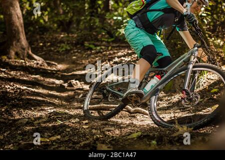 Mujer montando en bicicleta de montaña en pista forestal, Santa Cruz, California, Estados Unidos