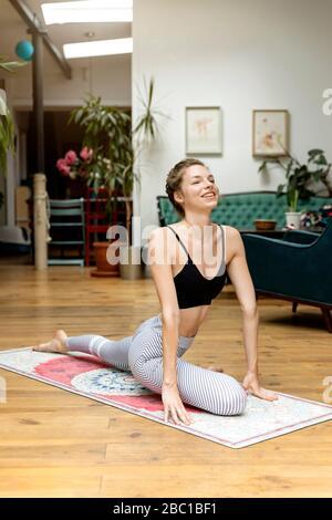 Mujer joven practicando yoga en su sala de estar