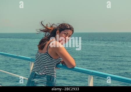 alegre chica joven con pelo negro en una camiseta a rayas y jeans azules se encuentra en la cubierta de un barco en el mar
