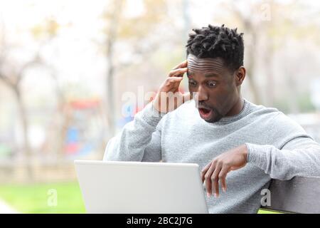 Hombre negro asombrado leyendo noticias sorprendentes en el ordenador portátil sentado en el banco del parque