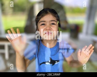 Volviendo a casa a la vida en un Bol de pescado. El padre fotógrafo preventivamente cuarentenas fuera de la casa e interactúa con su hija de 4 años a través de la puerta de vidrio del patio.