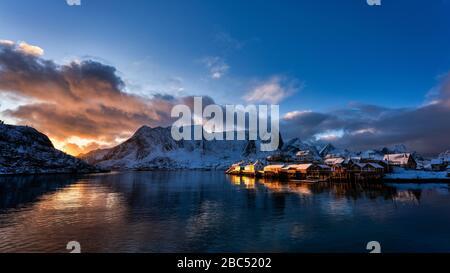 Luz de última hora de la tarde brillando en los edificios costeros, con reflejos en el agua y la montaña cubierta de nieve al fondo.