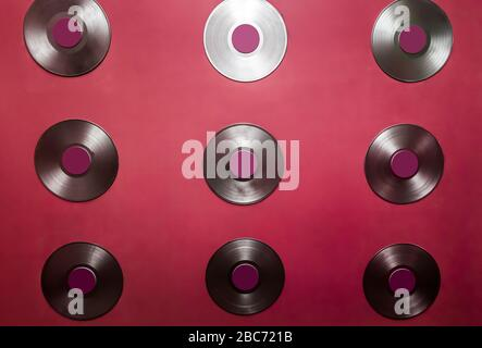 Los discos de vinilo viejos cuelgan en una pared roja.