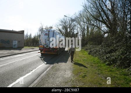 Estrasburgo, Francia - 18 de marzo de 2020: Vista trasera de una hermosa mujer sola caminando en el trottoir con Mauffrey camión en la calle