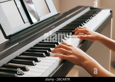 Manos de niño tocando piano.Cllose-up piano, blanco y negro teclado