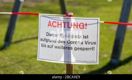 Cerca de la señal en el patio cerrado (Spielplatz). Con una palabra típica alemana: Achtung! (¡atención!). Restricciones debidas a Covid-19 / Coronavirus.