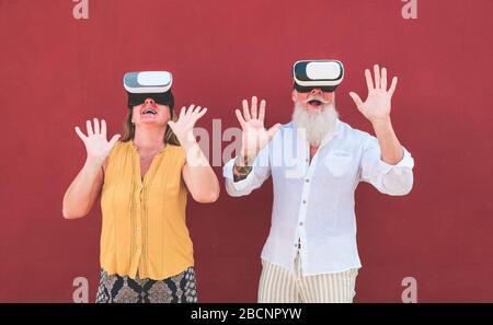 Pareja adulta divirtiéndose con la tecnología de gafas de realidad virtual - gente mayor que practica surf en línea mientras lleva auriculares vr - Tech, estilo de vida moderno y.