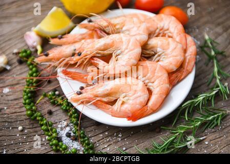 camarón fresco sobre plato blanco con ingredientes hierbas y especias / mariscos de cocina camarones gambas servidas sobre una mesa de madera