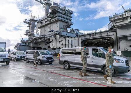 Los marineros de la Marina de los EE.UU. Asignados al portaaviones USS Theodore Roosevelt que han probado negativo para COVID-19 son transportados desde la base Naval de Guam al Gobierno de Guam alojamiento seguro el 3 de abril de 2020 en el Puerto de Apra, Guam. Los marineros deberán permanecer en cuarentena por lo menos 14 días. Anteriormente, el comandante de los buques Capt Brett Crozier fue relevado del servicio el 31 de marzo de 2020 después de pedir ayuda para detener la propagación de los casos COVID-19 en su buque.