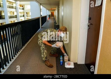 Un marinero de la Marina de los Estados Unidos entrega comida a las habitaciones de hotel donde los marineros del portaaviones USS Theodore Roosevelt que han probado negativo para COVID-19 están en cuarentena el 3 de abril de 2020 en Tamuning, Guam. Los marineros deberán permanecer en cuarentena por lo menos 14 días. Anteriormente, el comandante de los buques Capt Brett Crozier fue relevado del servicio el 31 de marzo de 2020 después de pedir ayuda para detener la propagación de los casos COVID-19 en su buque.