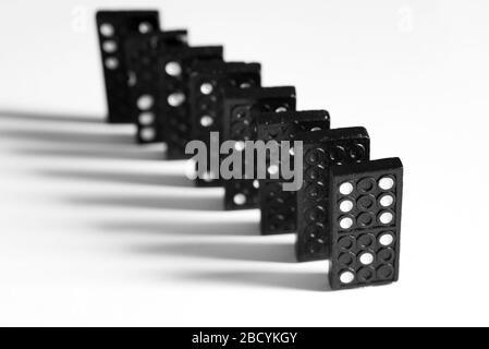 Bloques de dominó negros con puntos formando una diagonal aislada sobre fondo blanco Foto de stock