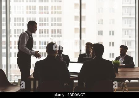 Siluetas de personas sentadas en la mesa. Un equipo de jóvenes empresarios trabajando y comunicándose juntos en una oficina. Empresas de negocios y Foto de stock