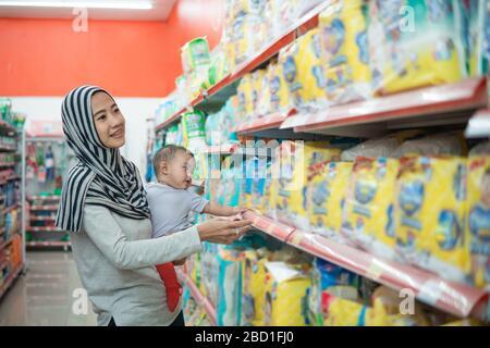 madre musulmana asiática que compra el producto del bebé mientras que lleva a su hija