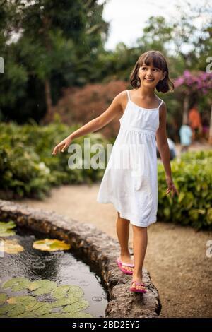 Sonriente joven divirtiéndose equilibrio sobre el muro de piedra de un estanque de jardín.