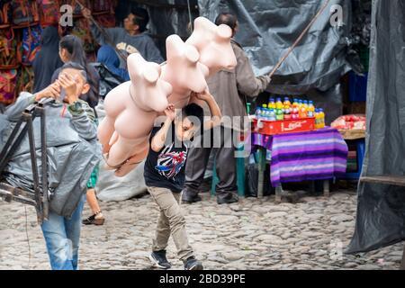 El joven lleva maniquíes al puesto de su familia en el mercado de Chichicastenango, Guatemala.
