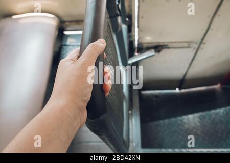 Mano agarrando el pasamanos sucio en el autobús de transporte público, riesgo de contaminación con gérmenes virus bacterias y patógenos. Concepto de brote de coronavirus