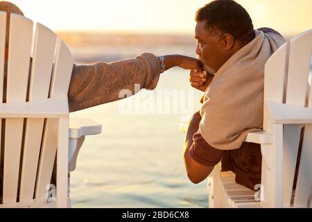 Feliz hombre mayor besando cariñosamente la mano de su esposa.