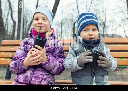 Dos adorables hermanos niños sentados en un banco de madera y bebiendo chocolate caliente, té o cacao de tazas de papel durante el paseo por el parque urbano