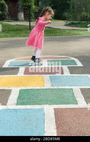 Joven linda chica jugando hopscotch en el patio trasero