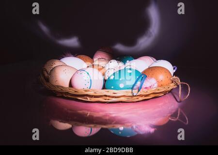 Coloridos huevos de pollo y codorniz con plumas en placa de paja sobre fondo brillante con luz rosada. Concepto de Pascua.