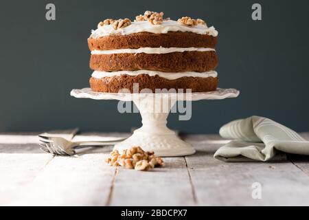Pastel de zanahoria de tres niveles con helado en soporte para tartas Foto de stock