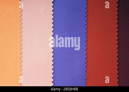 Muestras de telas en tonos pastel. Tela azul, roja, amarilla con textura. Tejido ligero de fibras sintéticas (nylon o poliéster) Foto de stock