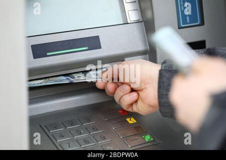 Manos masculinas que sostienen un montón de billetes de cien dólares en la máquina atm Foto de stock