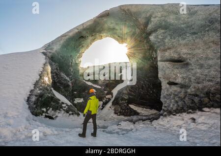 Hombre bajo un arco de hielo de Breidamerkurjokull, Austurland, Islandia, Norte de Europa