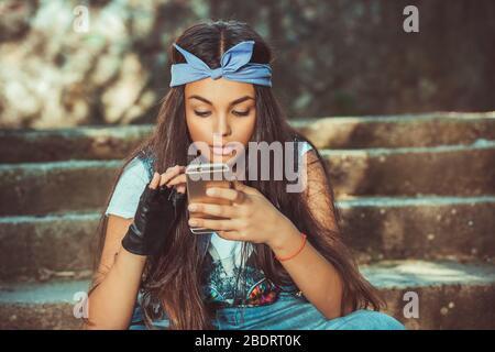 Mensajes de texto, lectura de sms. Joven niña estudiante mirando el teléfono móvil concentrándose a medida que introduce datos en la pantalla táctil con su dedo verde outdo