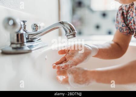 Vista de cerca de niños pequeños lavándose las manos con jabón en el fregadero