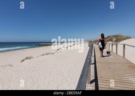 Mujer y perro caminando en el paseo marítimo de madera en la playa de Costa Nova do Prado Ilhavo cerca de Aveiro Portugal. Foto de stock
