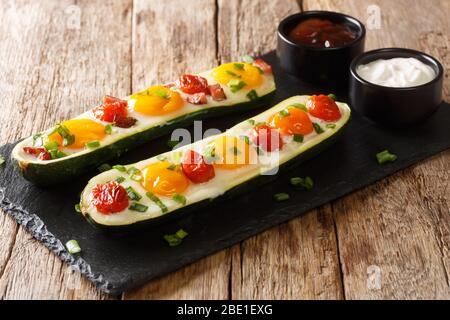 Desayuno de calabacín horneado con huevos, tomates de cerca sobre una pizarra en la mesa. Horizontal